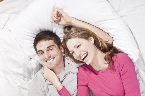 Young couple lying on bed, smiling - SSF00021