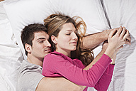 Young couple lying on bed, eyes closed - SSF00018