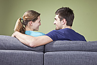 Young couple sitting on couch, smiling at each other, rear view - SSF00015