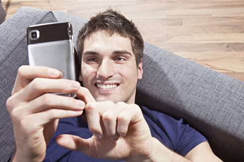 Man text messaging on mobile phone, smiling, close-up - SSF00012