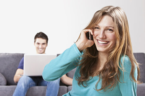 Woman talking on mobile phone, man using laptop in background - SSF00009