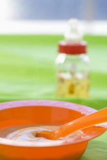 Baby food in bowl with baby bottle in background - SMOF00387