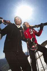 Italy, Alto Adige, Couple carrying ski, looking away, smiling - KEF00010