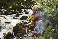Austria, Steiermark, Young couple sitting at camp fire by stream in forest - HHF03267