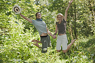 Young couple holding hands, jumping in forest - HHF03255