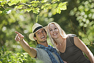 Young couple in forest, man pointing away - HHF03252