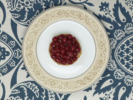 Raspberry tartlet in plate against patterned background - AKF00147