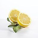 Cross section of lemon with leaf on white background - SRSF00019