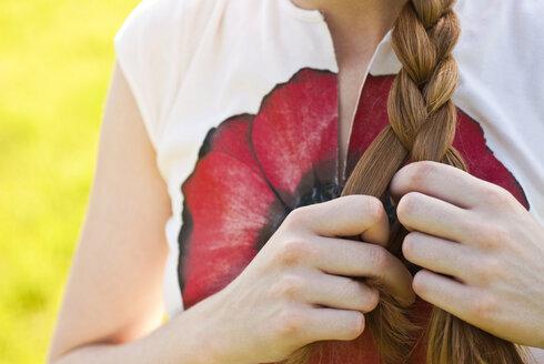Germany, Bonn, Woman braiding hair, mid section - KJF00079