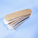 Stack of band-aids on blue background - SRSF00092
