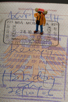 Figurine of man standing on passport - AWDF00539