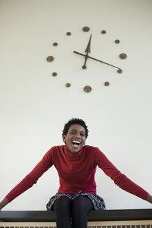 Germany, Leipzig, University student sitting against wall clock - BABF00604