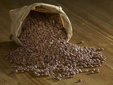 Mountain lentils spilling on wooden surface - SRSF00161