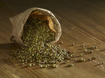 Brown mung beans spilled on wooden surface - SRSF00149