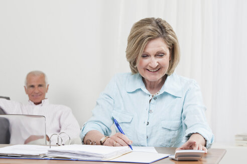 Woman doing paperwork with man sitting in background - CLF00849