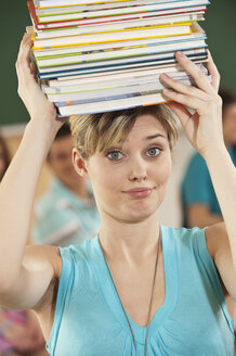 Germany, Emmering, Young woman carrying stack of books with students in background - RNF00325