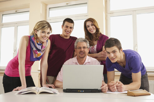 Germany, Emmering, Teacher and students using laptop, smiling, portrait - RNF00301