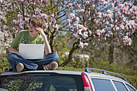 Germany, Boy sitting on car roof with laptop and magnolia tree in background - WDF00737