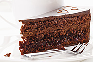Slice of Sacher cake in plate with coffee cup in background - 13330CS-U