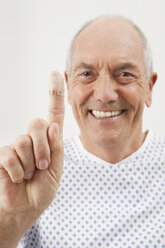 Germany, Munich, Mature man showing finger with bandage, close-up - WESTF14828