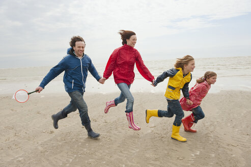 Germany, St. Peter-Ording, North Sea, Family holding hands and running on beach - WESTF15052