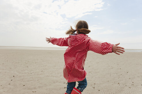 Germany, North Sea, St.Peter-Ording, Girl (6-7) in rain coat playing on beach, rear view - WESTF15037