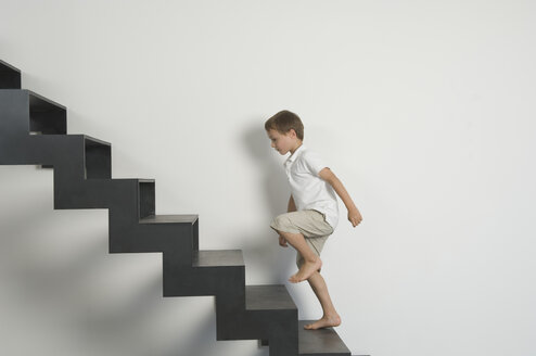 Germany, Boy (4-5 years) moving up from stairs - CRF001915
