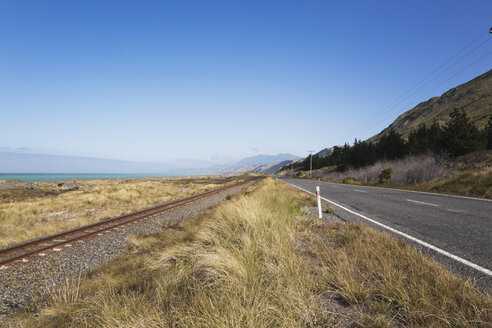 New Zealand, South Island, Canterburg, Kaikoura, View of main road with railway tracks and sea in background - GWF001211