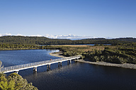New Zealand, South Island, West Coast, Man crossing bridge with mountains in background - GWF001320