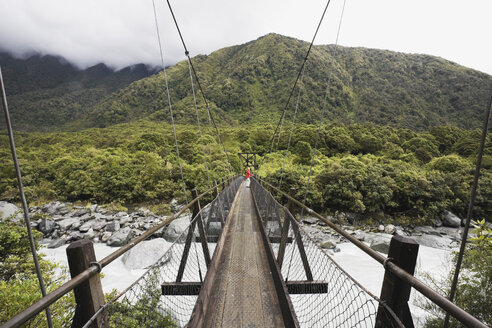 New Zealand, South Island, Woman crossing fox river through swing bridge - GWF001275