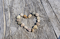 Germany, Northsea, Amrum, Close up of stones in heart shape on wood bench - AWDF000586