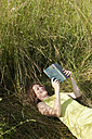Germany, Munich, Woman lying on grass and reading book - LDF000888
