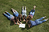 Germany, Munich, Man and woman lying on grass and reading book - LDF000879
