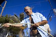 Greece, Crete, Paleochora, Senior man washing carGreece, Crete, Paleochora, Senior man washing car - MSF002401