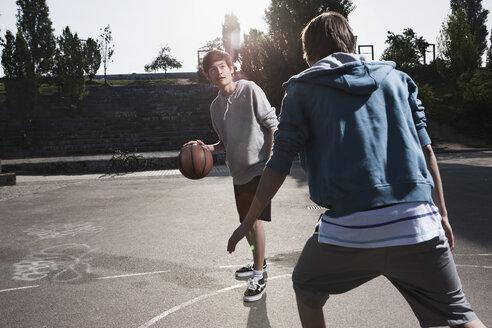 Germany, Berlin, Teenage boys playing basketball in playground - WESTF015325
