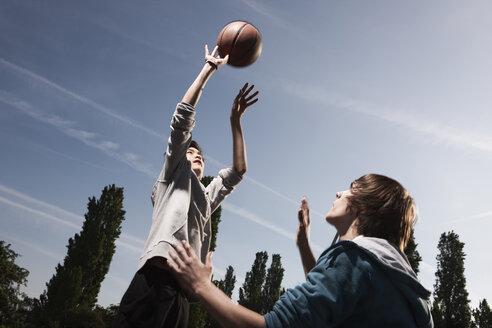 Germany, Berlin, Teenage boys basketball in playground - WESTF015346