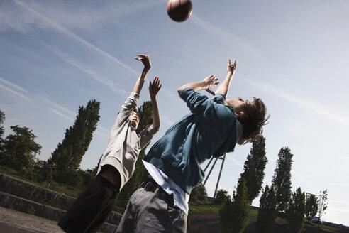 Germany, Berlin, Teenage boys basketball in playground - WESTF015355