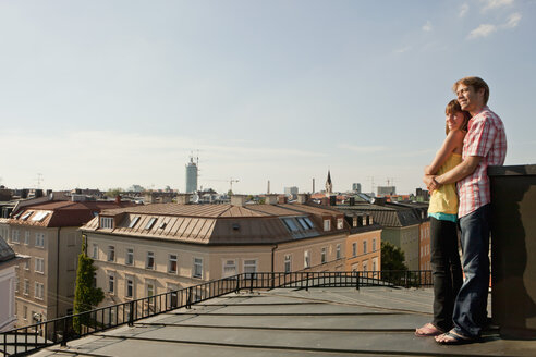 Germany, Bavaria, Munich, Young couple enjoying on rooftop with city in background - SKF000384