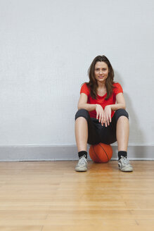 Germany, Berlin, Young woman sitting on basketball in school gym, smiling - BAEF000106