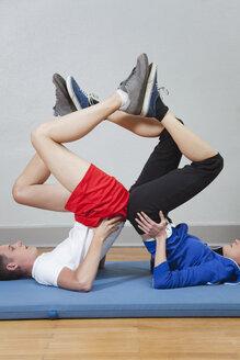 Germany, Berlin, Man and woman balancing on mat - BAEF000112