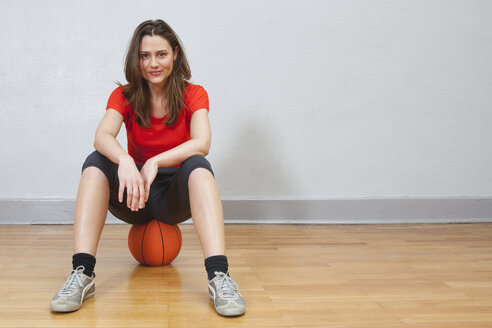 Germany, Berlin, Young woman sitting on basketball in school gym, smiling - BAEF000157