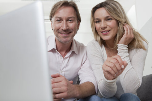 Couple using laptop, smiling - LDF000892
