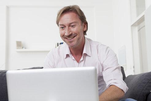 Man using laptop, smiling - LDF000901