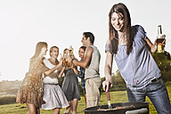 Germany, Cologne, Woman barbecueing with friends in background - JOF000142