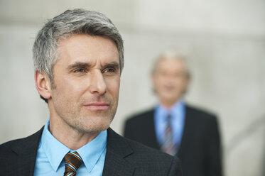 Germany, Hamburg, Businessmen, mature man looking away in foreground - WESTF015468