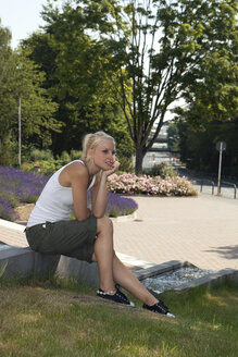 Germany, Dortmund, Young woman sitting and looking away - SKF000269
