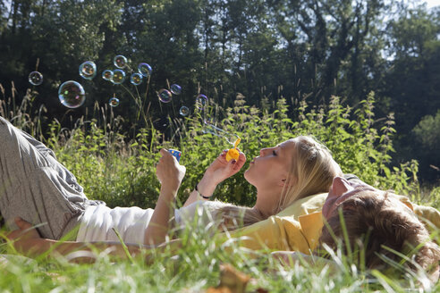 Germany, Dortmund, Young woman blowing bubble with lying on man - SKF000272
