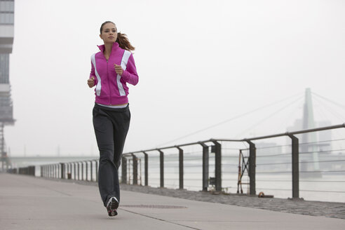 Germany, Cologne, Young woman jogging - SKF000347