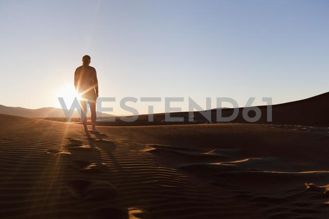 Africa, Namibia, Namib Naukluft National Park, Man walking on sand in the namib desert - FOF002473