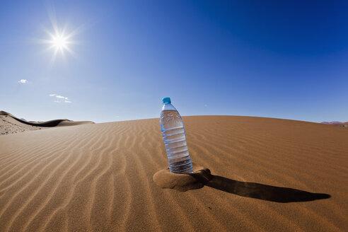 Africa, Namibia, Namib Desert, Water bottle on sand in namib-naukluft national park - FOF002396